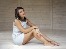 Girl  sitting on the floor. Girl in white sitting on the floor Royalty Free Stock Images
