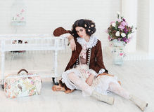 Girl sitting on the floor with the bag. Girl sitting on the white floor with the bag Royalty Free Stock Photography