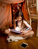 Girl sitting on floor at bedroom and reading book with flashligh Royalty Free Stock Photo
