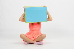 Girl sitting the floor with a box on his head Royalty Free Stock Photos