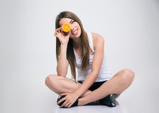 Girl sitting on the floor and covering one eye with orange Royalty Free Stock Photography