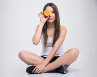Girl sitting on the floor and covering one eye with orange Royalty Free Stock Image