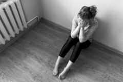Lonely girl is sitting on the floor and crying covering her face with her hands, black and white photo. The girl is sitting on the floor and crying covering her royalty free stock photography