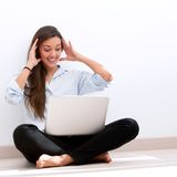 Girl sitting on floor with laptop Stock Image