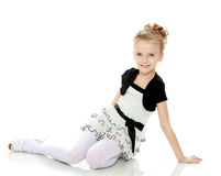 Girl sitting on the floor leaning on hand and looking to the sid Royalty Free Stock Photos