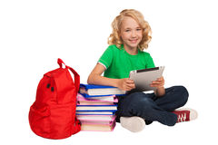 Girl sitting on the floor near books and bag holding tablet Royalty Free Stock Images