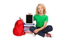 Girl sitting on the floor near books and bag holding tablet. Little blonde girl sitting on the floor near books and bag holding tablet Royalty Free Stock Photography