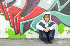 Girl sitting on the floor near graffiti wall Royalty Free Stock Image