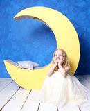 Girl sitting on the floor near the moon. Royalty Free Stock Images