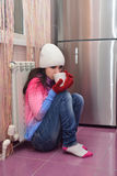 Girl sitting on the floor next to a radiator and drinking tea Stock Images