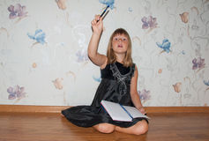 Girl sitting on the floor with notebook and pen. Have idea Stock Photography