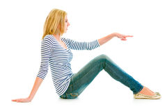 Girl sitting on floor and pointing at copy-space stock image