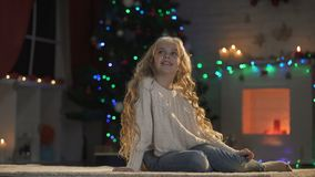 Girl sitting on floor in room decorated for X-mas, waiting Santa, holiday magic. Stock footage stock video