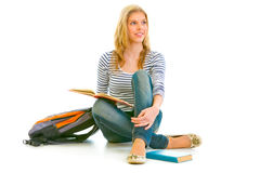 Girl sitting on floor with schoolbag and books Stock Photos