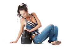Girl sitting on floor and sees bag Stock Photo