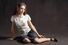 Girl sitting on floor in skirt black background Royalty Free Stock Photo