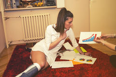 Girl sitting on a floor and studying Stock Photography