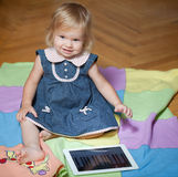 Girl sitting in the floor with tablet computer Royalty Free Stock Photos