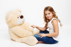 Girl sitting on floor with toy bear holding his paw. royalty free stock images