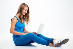 Girl sitting on the floor and using laptop Royalty Free Stock Photo