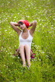 Girl sitting in flower meadow Royalty Free Stock Photography