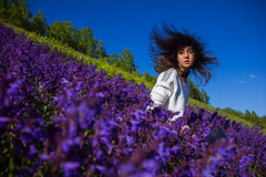 Girl sitting on a flower meadow Stock Photos