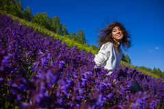 Girl sitting on a flower meadow Stock Image