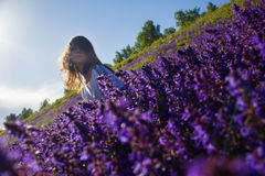 Girl sitting on a flower meadow Royalty Free Stock Photography