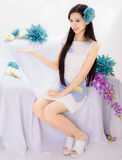 Girl sitting on flower sofa Royalty Free Stock Images