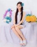 Girl sitting on flower sofa Stock Image