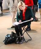 Girl sitting on folding stool sketching at the British Museum London England 1 - 10 - 2018. Blond girl sitting on folding stool sketching at the British Museum Royalty Free Stock Photos