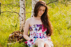 Girl sitting a forest glade and reading book Royalty Free Stock Photography