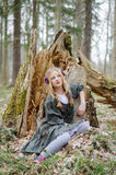 Girl sitting in the forest near crashed tree Stock Photos