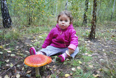 Girl sitting in a forest near the fly agaric Stock Images