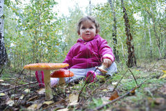 Girl sitting in a forest near the fly agaric Royalty Free Stock Image