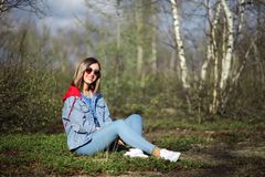 Girl sitting in the forest. Pretty young girl sitting in the spring forest stock photos