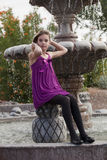 Girl Sitting by a Fountian in Purple Dress Royalty Free Stock Photography