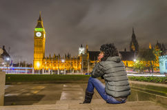 Girl sitting in front of Big Ben and House of Parliament. Beautiful girl takes rest looking at amazing big ben and house of parliament view, London, UK Stock Photo