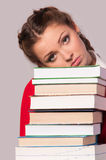Girl sitting in front of books Stock Images