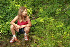 Girl sitting in front of a bush Stock Images