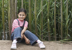 Girl Sitting In Front Of Fence Royalty Free Stock Photography