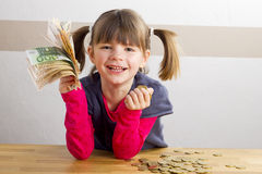 Girl sitting in front of a lot of money Royalty Free Stock Photography