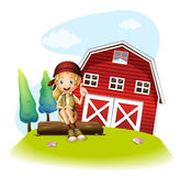 A girl sitting in front of a red barnhouse Royalty Free Stock Images