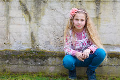 Girl sitting in front of a wall Royalty Free Stock Images