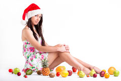 Girl sitting between fruits Stock Image