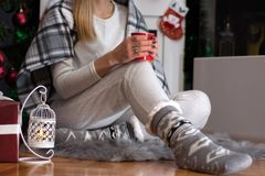 Girl sitting on furry carpet in home clothes and Christmas socks royalty free stock images