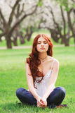 Girl sitting in the garden Stock Photos