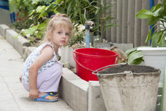 The girl sitting in the garden next to the bucket and the crane Royalty Free Stock Images