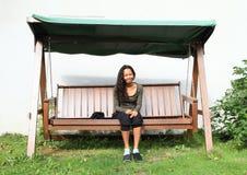 Girl sitting on a garden swing Stock Image