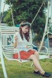 Girl sitting on garden swing